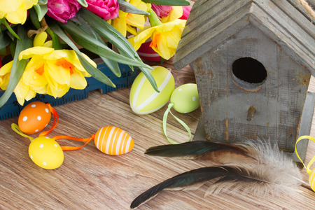 birdcage: wooden birdcage with spring tulips and daffodils  and easter eggs Stock Photo