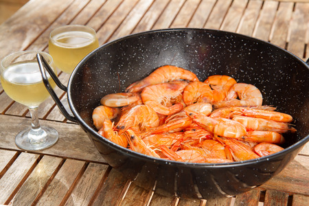 red cooked: black pan with  red cooked  prawns on wooden table