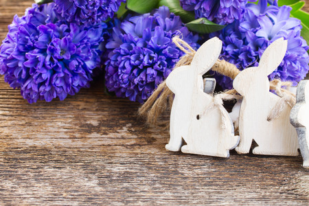 withe easter rabbits and hyacinth flowers on table photo