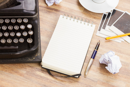 ruled: empty ruled notebook with frame of black vintage typewriter and coffee on table