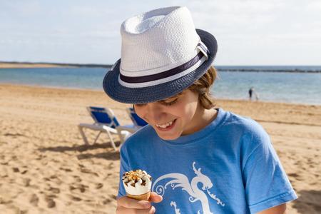 comiendo helado: muchacho que come el helado en la playa