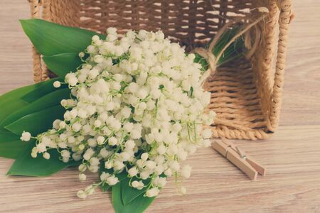 posy: lilly of the valley flowers posy in basket  on wooden background, retro toned