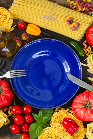 ingridients: Raw pasta with ingridients and copy space on empty blue plate Stock Photo