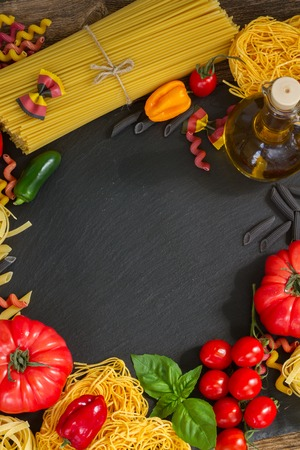 ingridients: Raw pasta with ingridients on black board