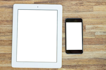 tablet and phone on wooden table with copy space on screen photo