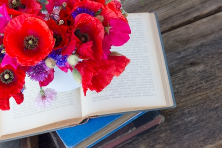 field of flowers: stack of vintage old books  on table with field flowers