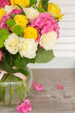 hydrangea flower: pink hortensia flowers with white and yellow roses in vase  close up