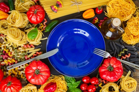 ingridients: Raw pasta with ingridients and copy space on empty blue plate with steel fork and knife