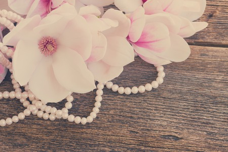 table decoration: magnolia fresh flowers with pearls  on wooden table, retro toned Stock Photo