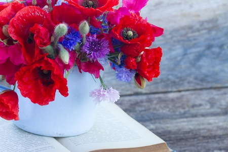 field of flowers: stack of vintage old books  on table with fresh  field flowers