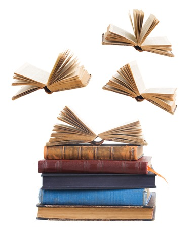 libros abiertos: Tower of old books and flying open books isolated on white background