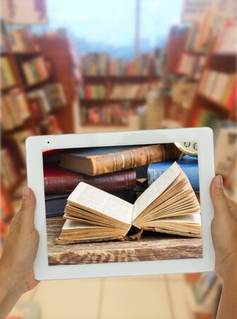 shelfs: Hands holding  tablet with open book on screen library shelfs in background, e-learning concept Stock Photo