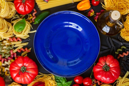 ingridients: Pasta with ingridients and blank blue plate Stock Photo
