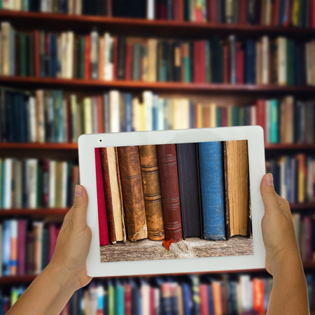 library old: Hands holding  tablet with row of books on screen, library shelfs in background, e-learning concept