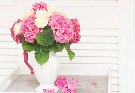 roses in vase: pink fresh hortensia flowers with white roses in vase on table Stock Photo