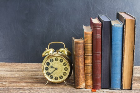 antique books: row of  old books with antique alarm clock  on wooden shelf Stock Photo