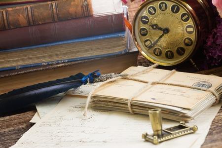 책과 메일의 더미와 함께 골동품 알람 시계 스톡 콘텐츠