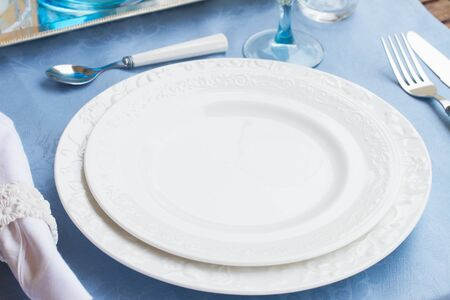 utencils: Tableware - set of plates, cups and utencils on blue tablecloth