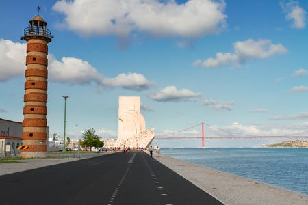 25th: Lighthouse with the Monument to the Discoveries in Lisbon and bridge of 25th April by riverbank of Tagus, Lisbon, Portugal