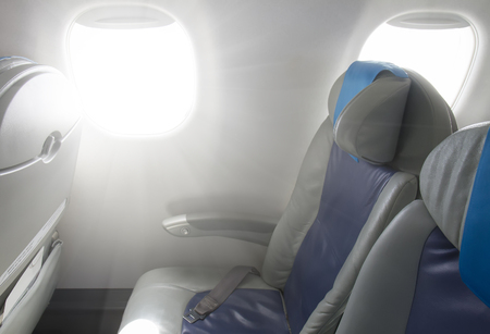 window light: Cabin of plane with chairs and window close up Stock Photo