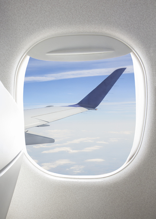Plane window with view of sky and wing