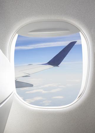 Vliegtuig raam met uitzicht van de hemel en de vleugel