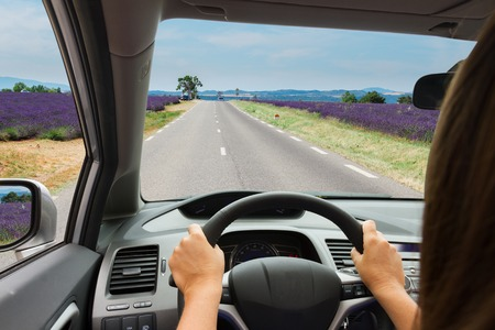 woman driving: woman driving a car on country road, view  inside out Stock Photo