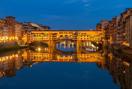 river arno: famous bridge Ponte Vecchio with reflection in  river Arno at night, Florence, Italy