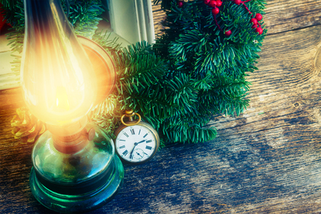 old fashioned christmas: vintage glowing lantern with christmas evergreen wreath and antique watch, low key Stock Photo