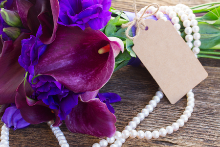 white callas: Ramo de Lilly de la cala y eustoma flores en la mesa de madera con la etiqueta de papel vac�a Foto de archivo