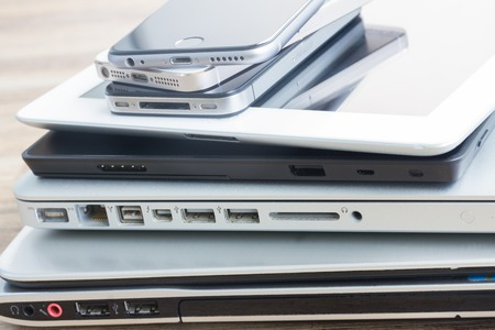 heap  of modern glossy electronical devices  - technology concept