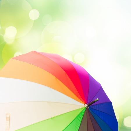beautiful umbrella: Open rainbow umbrellas  over green garden  background Stock Photo