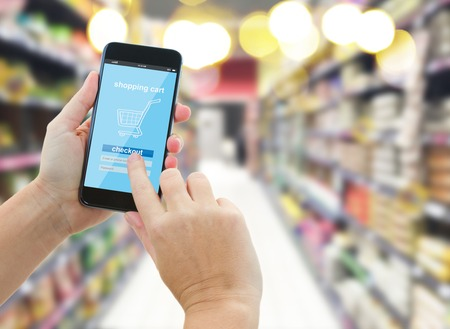 grocery shelves: woman hands holding mobile smart phone with mobile shop  on supermarket blur background  - e-commerce concept Stock Photo