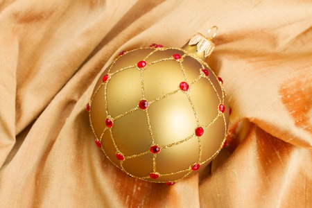 christmas bow: golden and red  christmas  ball on soft silk background Stock Photo