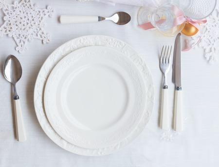プレートとクリスマスの装飾と白いテーブル クロスの上の器具