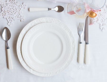 breakfast plate: Plates and utensils on white tablecloth with christmas decorations