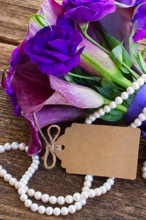 calas blancas: Ramo de la cala lilly y eustoma flores en la mesa de madera con la nota de papel vac�o