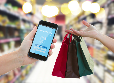 consumer products: hand holding mobile smart phone with mobile shop  on supermarket blur background and shopping bags - e-commerce concept