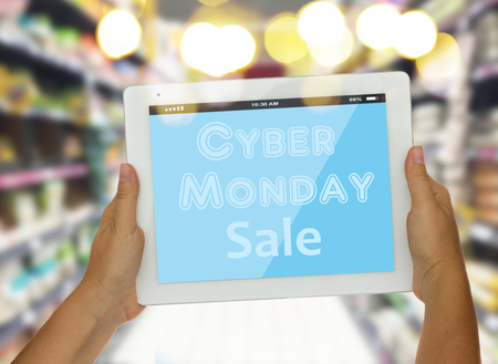 someones hand holding  modern tablet with cyber monday sale words