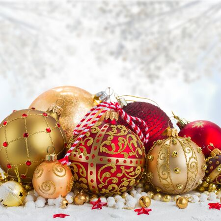 heap of snow: Heap of christmas  balls in gold  and red colors  in snow on gray bokeh  background
