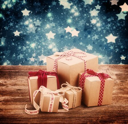 stary: Handmade gift boxes on wooden table, stary night at background, retro toned