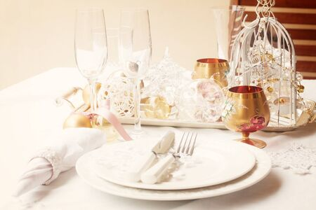 utencils: Tableware for christmas - set of plates, cups and utencils  with white table cloth and christmas golden decorations, retro toned