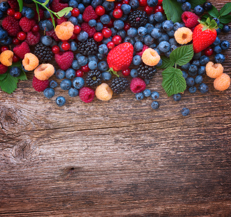 border of fresh  berries mix on wooden tabletop with copy space, retro toned 版權商用圖片
