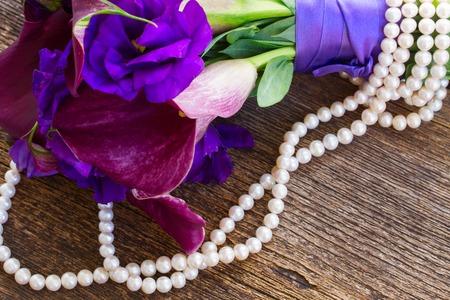 White Callas: Ramo de la cala lilly fresca y eustoma flores de cerca en la mesa de madera