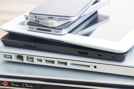 electronical: heap  of modern glossy electronical devices close up - technology concept