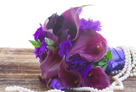calas blancas: Bouquet of calla lilly and eustoma flowers close up on wooden table isolated on white background