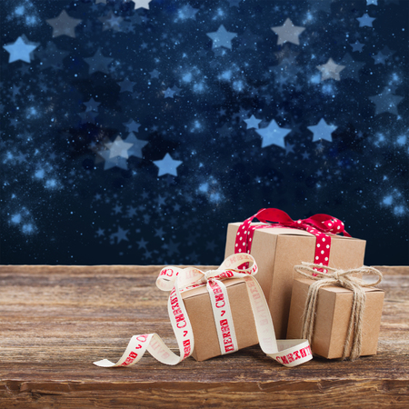 stary: Pile of Handmade gift boxes on wooden table, stary night at background Stock Photo