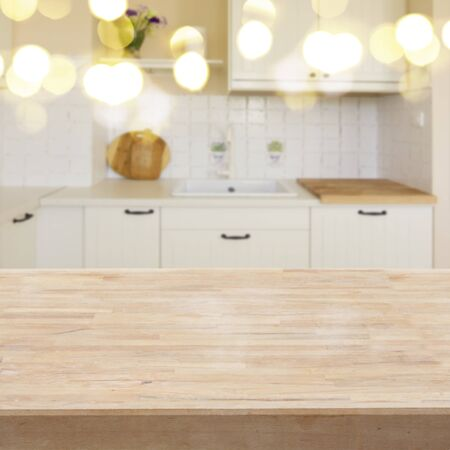 withe: empty wooden table in a withe modern kitchen with bokeh lights in background