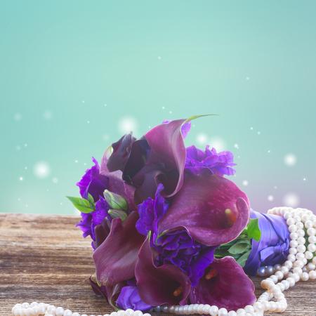 calas blancas: Ramo de la cala lilly y eustoma flores de cerca en la mesa de madera, fondo azul