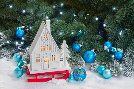 holiday house: White christmas house on sledge with blue decorations in snow